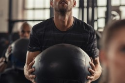 Man carrying weighted exercise ball in group gym session